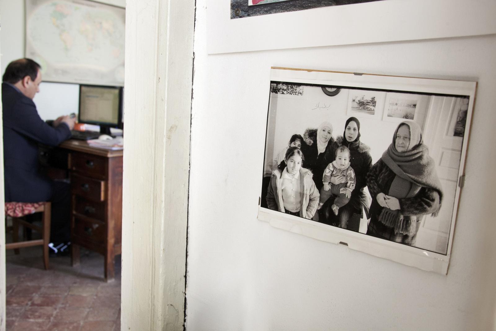 Il signor Sindaco e la Città Futura | Gianfranco Ferraro - Foto di una delle prime famiglie migranti arrivate a Riace. Sullo sfondo, a sinistra, il sindaco Domenico Lucano al lavoro nell'ufficio dell'Associazione Città Futura. © Gianfranco Ferraro.