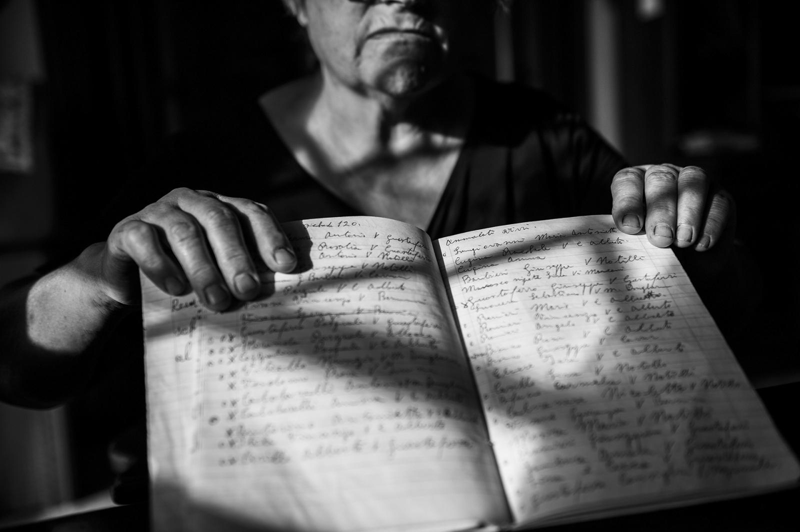 Rosa Bianco, 67 anni, mostra il diario sul quale dal 2013 sta censendo i malati di cancro del suo quartiere. Grazie al suo lavoro, Maria Rosaria Esposito, legale ambientalista, si sta battendo per aggiornare il registro tumori della Asl locale, Terzigno, NA, 2015. © Stefano Schirato.