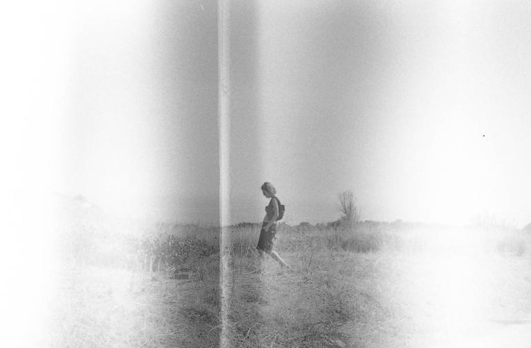 Mia sorella cammina da sola in campagna, Scansione da pellicola bianconero, Sicilia, 2011. © Anna Pizzoccaro.